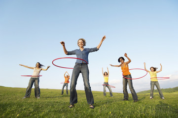 Group of friends using hula hoops in mountain field, low angle view