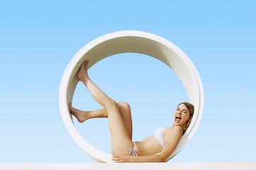 Young Woman in bikini lying in Tube, side view, portrait