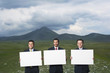 Three smiling businessmen standing in mountain field holding blank signs, front view