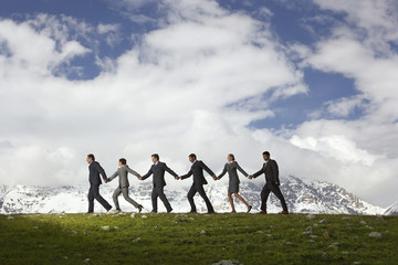 Business People Holding Hands and Walking through mountains, side view