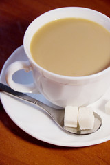 Coffee cup with white coffee and cubes of sugar