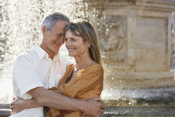 Middle-aged couple hugging by fountain, Rome, Italy, close up