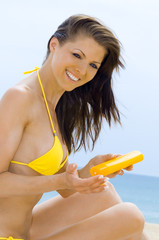 Hübschen Frau cremt sich mit Sonnencreme ein
