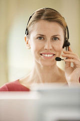 Mid-adult female office worker sitting in cubicle wearing headset, portrait