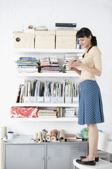 Businesswoman standing on chair reading book by shelves