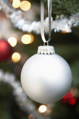 Silver bauble hanging from christmas tree, close up