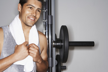 Sweaty man with towel  by weight machine after workout