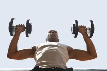 Man Lifting dumbbells, low angle view, close up
