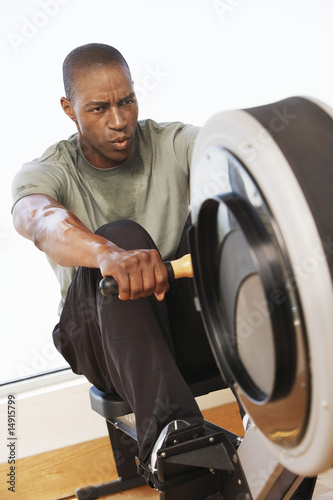 Man working out on Rowing Machine in health club