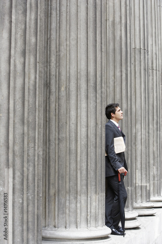 Businessman outside building looking up at sky