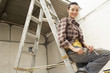 Female interior decorator sitting on ladder in work site, portrait, low angle view