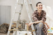 Female interior decorator sitting on ladder in work site, front view