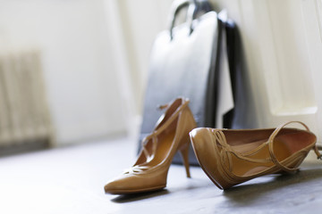 High heels and briefcase on domestic hallway floor, close up