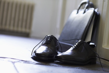 Dress Shoes and briefcase on domestic Hallway floor, close up