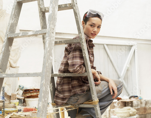 Female interior decorator sitting on ladder in work site, portrait