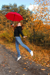 girl with umbrella in autumn forest