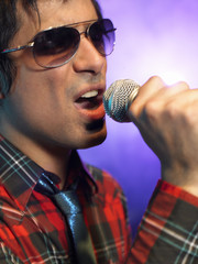 Young Man Singing into microphone on stage at Concert, close up