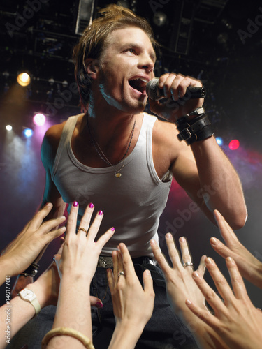 Low angle view of male rock star singing on stage with adoring fans reaching their hands up towards him