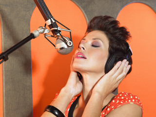 Young woman singing in studio, portrait