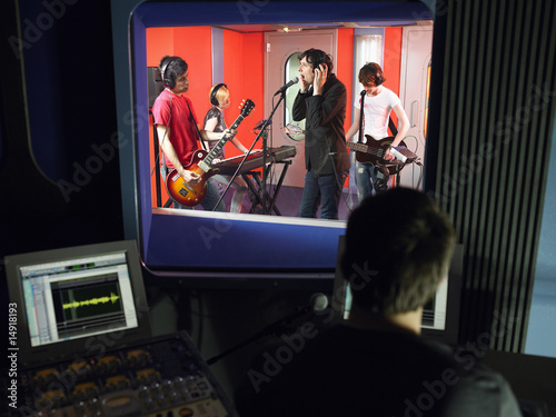 Band in recording studio, technician in foreground
