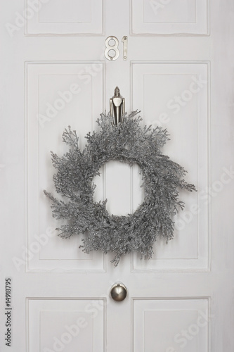 Christmas wreath hanging on white door