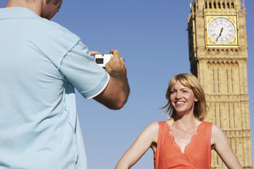 Husband taking photo of wife by Big Ben Tower, London, England