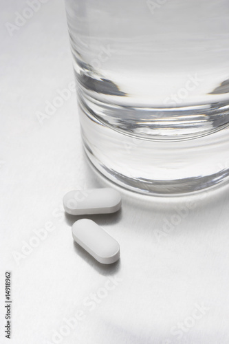 Two pills beside glass of water