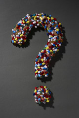 Various pills forming question mark, on black background