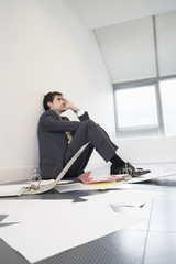 Stressed businessman sitting on floor of empty office by scattered files