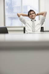 Businessman reclining in office chair looking at ceiling daydreaming