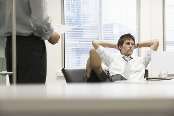 Disinterested businessman reclining on chair and ignoring boss in office