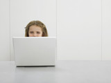 Small girl by desk using laptop