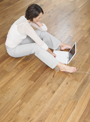 Woman sat on wood panel floor using laptop