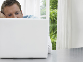 Man staring at laptop, window and garden behind