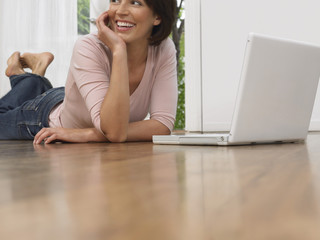 Woman laying on floor, using laptop