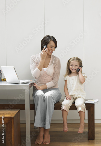 Mother and daughter using cell phones