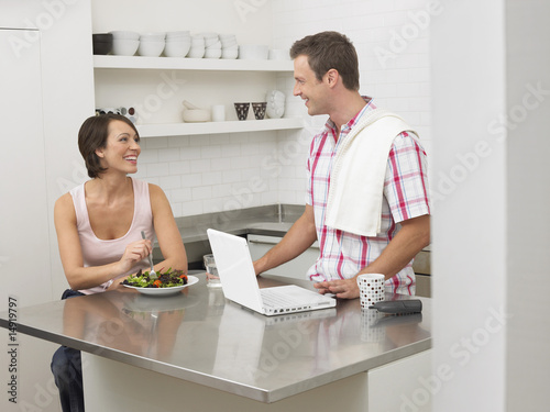 Couple in kitchen, woman eating, man using laptop