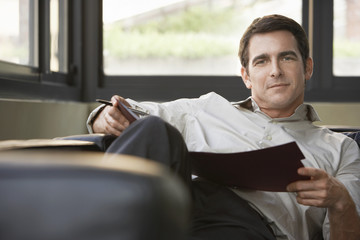 Relaxed portrait of successful mid adult businessman reclining on sofa with folder