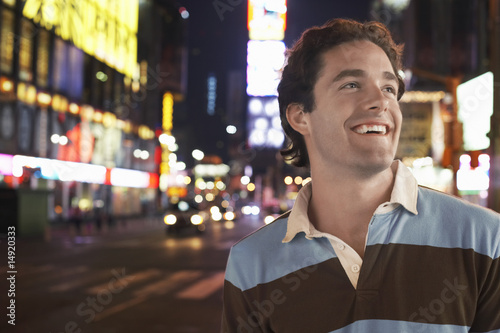 Young man standing in Times Square New York at night