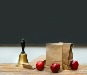 Lunch bags with apples and school bell on desk