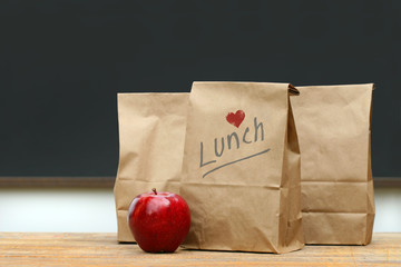 Lunch bags with  apple on school desk