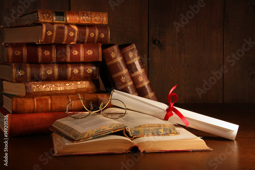 Pile of old books with glasses on desk