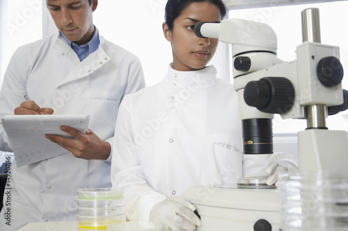 Female lab worker adjusting microscope, male lab worker writing behind