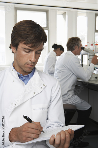Lab Worker writing, colleagues behind