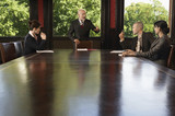 Businesspeople meeting around boardroom table, businessman standing