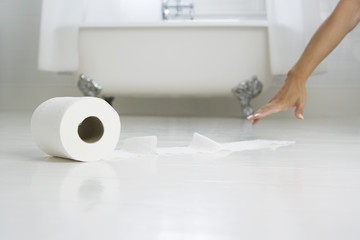 Woman reaching for toilet paper on bathroom floor