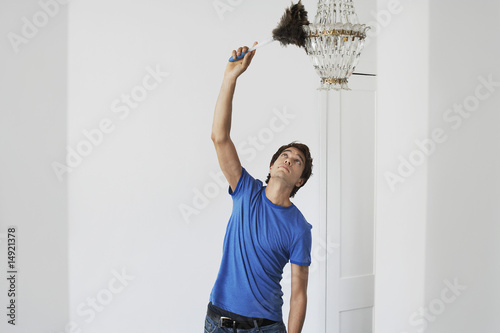 Man dusting crystal chandelier in home