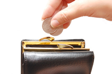 A hand dropping a coin inside a black purse