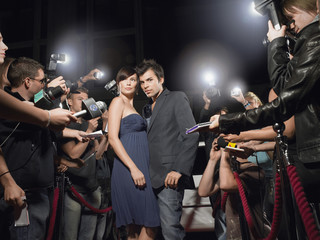 Couple posing on red carpet, being photographed by paparazzi