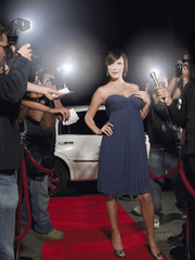 Woman posing on red carpet, being photographed by paparazzi
